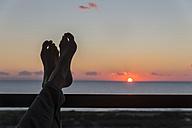 Greece, Peloponnese, woman's feet on railing by sunset - CHPF000013