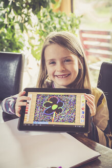 Portrait of smiling little girl showing digital tablet with her drawing - SARF001306