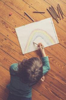 Girl lying on timber floor drawing rainbow - LVF002728