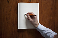 Man's hand writing with ballpen in notebook - RBF002433