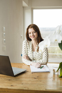 Smiling young woman with laptop at wooden table - UUF003208