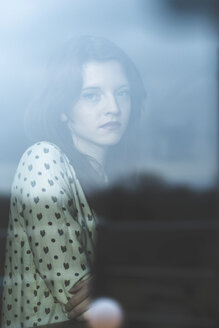Serious young woman behind windowpane - UUF003212