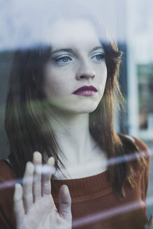 Serious young woman behind windowpane - UUF003226
