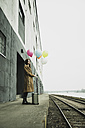 Young woman with suitcase holding bunch of balloons on platform - UUF003262