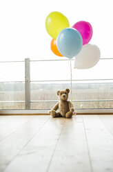 Bunch of balloons and teddy bear by the window - UUF003306