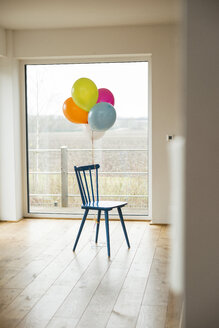 Bunch of balloons and chair by the window - UUF003309