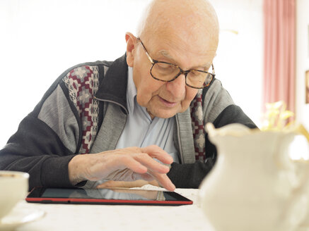 Old man sitting at table using digital tablet - LAF001311
