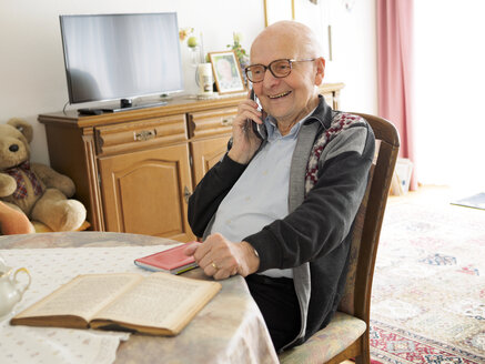 Old man sitting at table telephoning - LAF001322