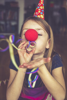 Little girl with clown's nose and cap blowing streamer - SARF001323