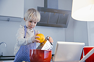 Little boy standing in the kitchen baking with help of digital tablet - MFF001473