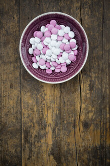 Bowl of pink and white chocolate buttons on wood - LVF002741