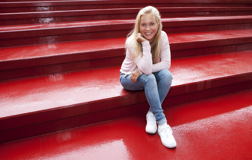 Portrait of smiling female teenager sitting on red stairs - WWF003759