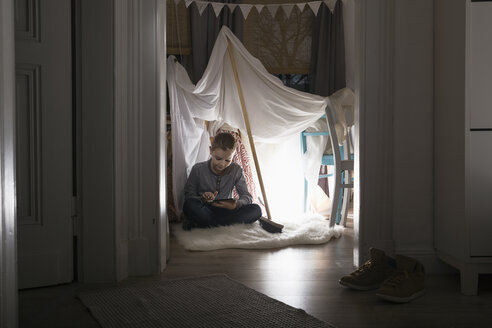 Boy sitting in self-made tent at home in the evening using digital tablet - PDF000682