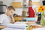Boy sitting at kitchen table with his homework - PDF000694