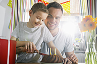 Father and son cutting birthday cake - PDF000748