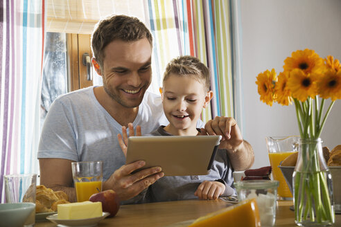 Father and son sitting at breakfast table using digital tablet - PDF000763