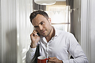 Portrait of businessman with cup of coffee telephoning at home - PDF000702