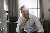 Portrait of smiling man at his home office - PDF000705