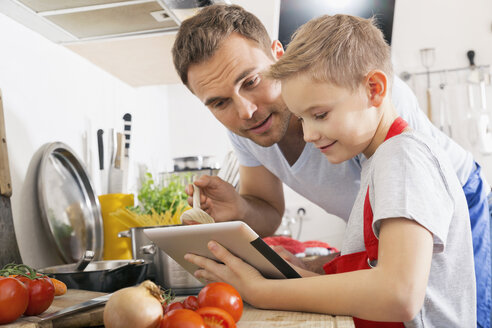 Father and son cooking together using digital tablet - PDF000765