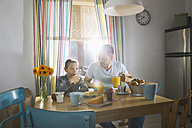 Father and son sitting at breakfast table - PDF000726