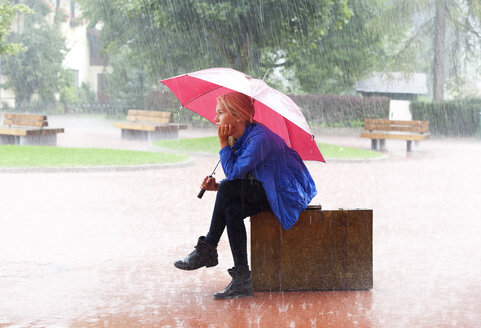 Austria, Thalgau, teenage girl with red umbrella sitting on her suitcase in the rain - WWF003771
