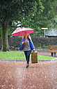 Austria, Thalgau, teenage girl with red umbrella walking in the rain with suitcase - WWF003773