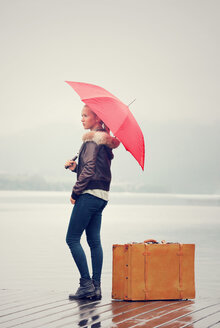 Austria, Mondsee, teenage girl with red umbrella standing in the rain with suitcase - WWF003776