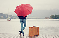 Austria, Mondsee, teenage girl with red umbrella standing in the rain with suitcase - WWF003777