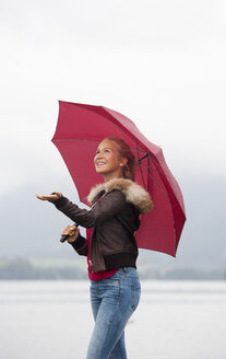 Austria, Mondsee, teenage girl with red umbrella standing at lakeshore - WWF003780