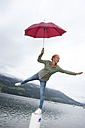 Austria, Mondsee, teenage girl with red umbrella balancing on a pole in front of lake - WWF003781