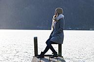 Austria, Mondsee, teenage girl sitting on jetty in autumn - WWF003807