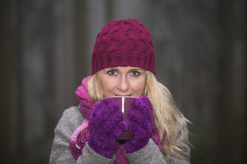 Austria, Mid adult woman drinking tea in winter, smiling - WWF003788
