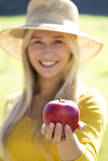 Portrait of smiling teenage girl offering a red apple - WWF003813