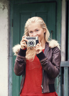Portrait of smiling teenage girl with old camera - WWF003801