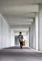 Man with leather suitcase running in a car park - WWF003714