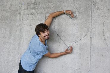 Man embracing graffiti heart on concrete wall - WWF003719