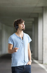 Young man hearing music with headphones - WWF003721