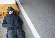 Man wearing hooded jacket sleeping beside lane - WWF003726