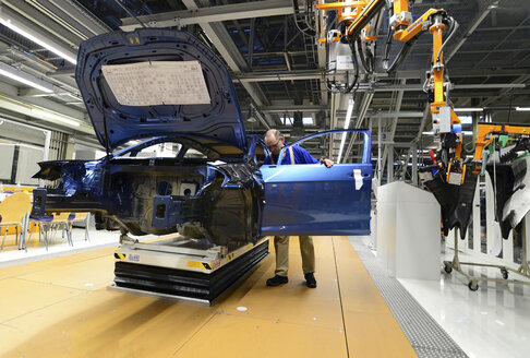 Production of VW cars in a factory, worker installing car door - SCH000450