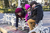 Spain, Gijon, three smiling children side by side in a park on a winter day - MGOF000058