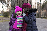 Girl telling another girl a secret in a park on a winter day - MGOF000063