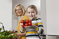Mother with daughter holding tomatoes in kitchen - RBF002387