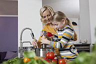 Mother and daughter cooking in kitchen - RBF002390