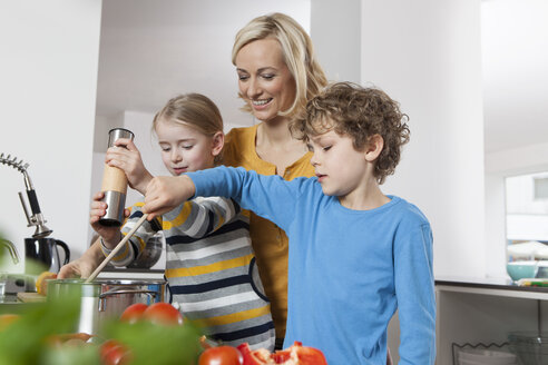 Mother, daughter and son cooking in kitchen - RBF002396