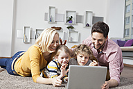 Happy family using laptop at home - RBF002405