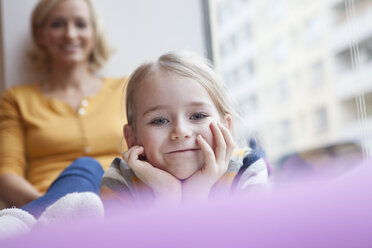 Smiling girl with mother in background - RBF002416