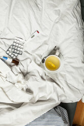 Lemon infusion, thermometer, pills, nasal spray and tissues in bed - SBDF001606
