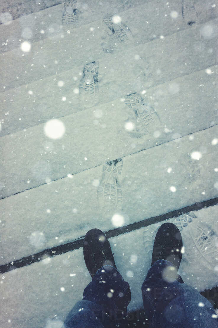 Man standing on snow covered stairs - DWIF000429 - Dirk Wüstenhagen/Westend61