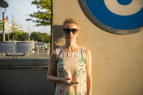 Germany, Berlin, woman standing in front of an underground sign - CHPF000043