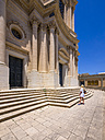 Italy, Sicily, Modica, Woman looking at San Giovanni church, UNESCO World heritage site - AMF003755